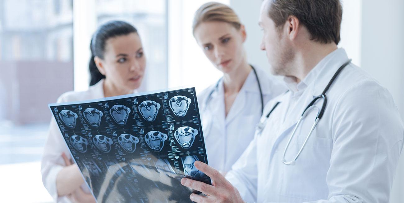 Médico mostra exame raio-x para outras duas colegas médicas