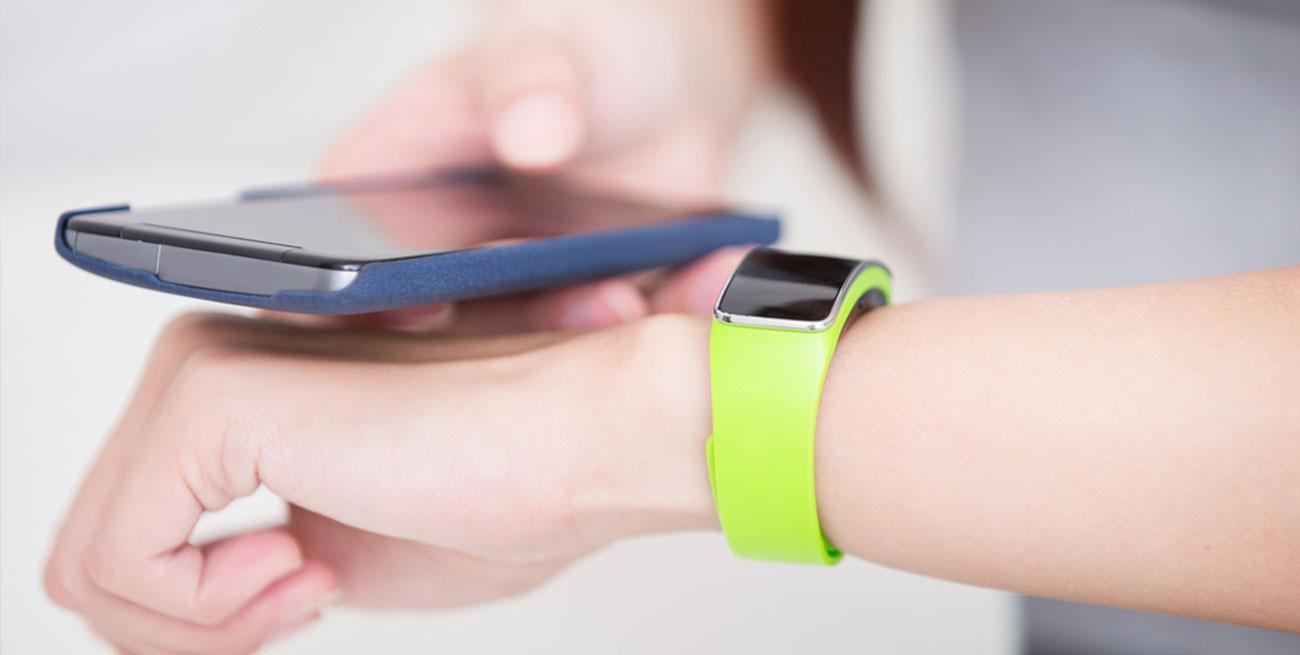 Mulher sincroniza smartwatch com smartphone